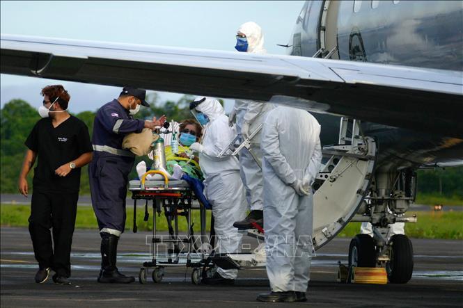 Nhân viên y tế chuyển bệnh nhân mắc COVID-19 lên máy bay tại Manaus, Brazil ngày 16-1-2021. Ảnh: THX/TTXVN