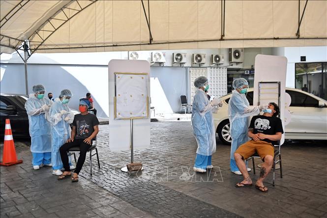 Nhân viên y tế lấy mẫu xét nghiệm COVID-19 tại Bangkok, Thái Lan. Ảnh: AFP/TTXVN