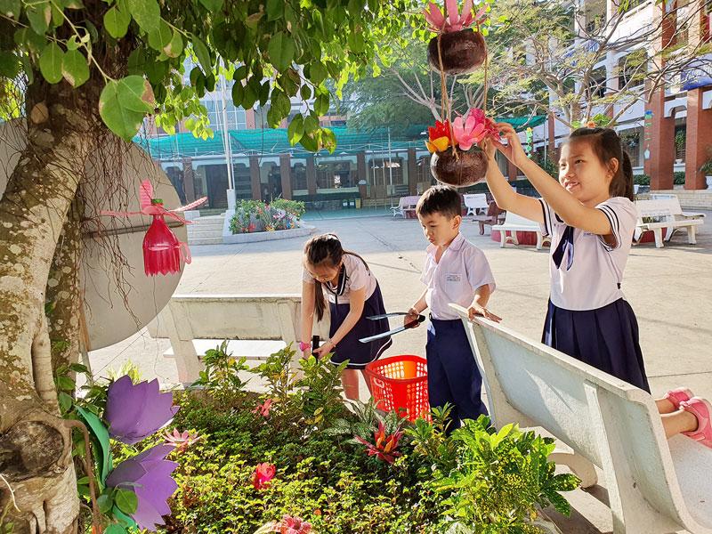 Học sinh Trường Tiểu học Chu Văn An chăm sóc bồn hoa trong khuôn viên trường.