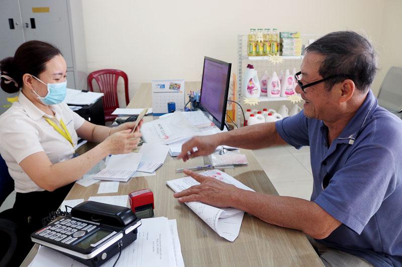 Nhân viên Bưu điện TP. Bến Tre thực hiện chi trả bảo trợ xã hội cho người dân. Ảnh: Phan Hân