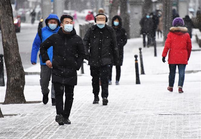 Người dân đeo khẩu trang phòng lây nhiễm COVID-19 tại Bắc Kinh, Trung Quốc, ngày 19-1-2021. Ảnh: THX/TTXVN