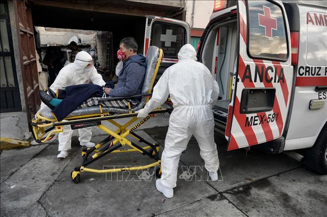 Nhân viên y tế chuyển bệnh nhân mắc COVID-19 lên xe cứu thương tại Toluca, Mexico ngày 8-1. Ảnh: AFP/TTXVN