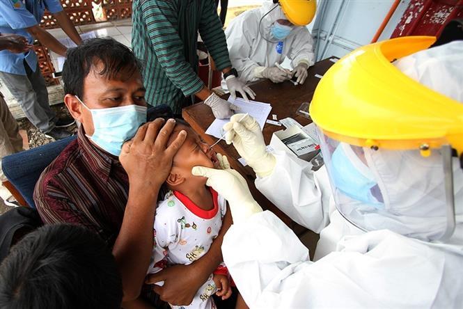 Nhân viên y tế lấy mẫu xét nghiệm COVID-19 tại Surakarta, Indonesia, ngày 21-1-2021. Ảnh: THX/TTXVN