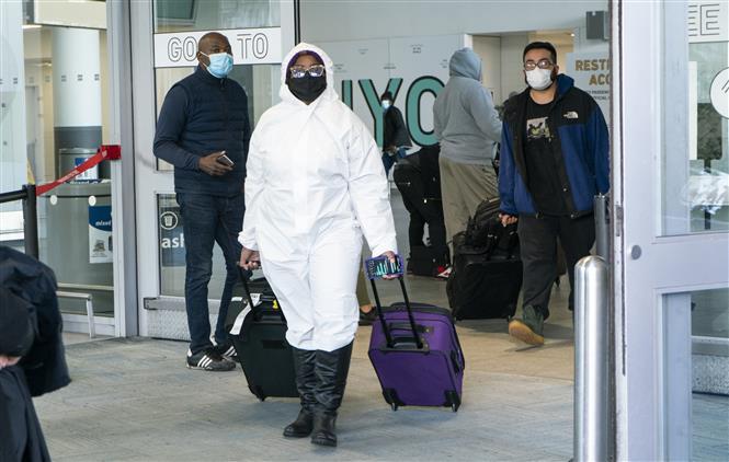 Hành khách đeo khẩu trang phòng lây nhiễm COVID-19 tại sân bay quốc tế JFK ở New York, Mỹ, ngày 22-12-2020. Ảnh: AFP/TTXVN