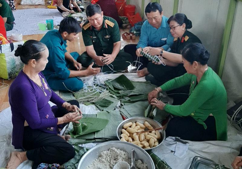 Cán bộ, chiến sĩ Ban Chỉ huy Quân sự huyện Chợ Lách cùng tham gia gói bánh tét với người dân. Ảnh: Văn Thiện