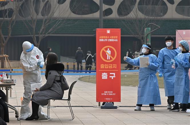 Nhân viên y tế lấy mẫu dịch xét nghiệm COVID-19 cho người dân tại Seoul, Hàn Quốc, ngày 23-12-2020. Ảnh: AFP/ TTXVN