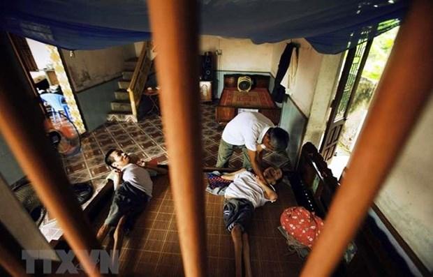 Ông Lại Văn Biên (huyện Vũ Thư, Thái Bình) chăm sóc cho hai con trai bị ảnh hưởng bởi chất độc da cam. (Ảnh: TTXVN)