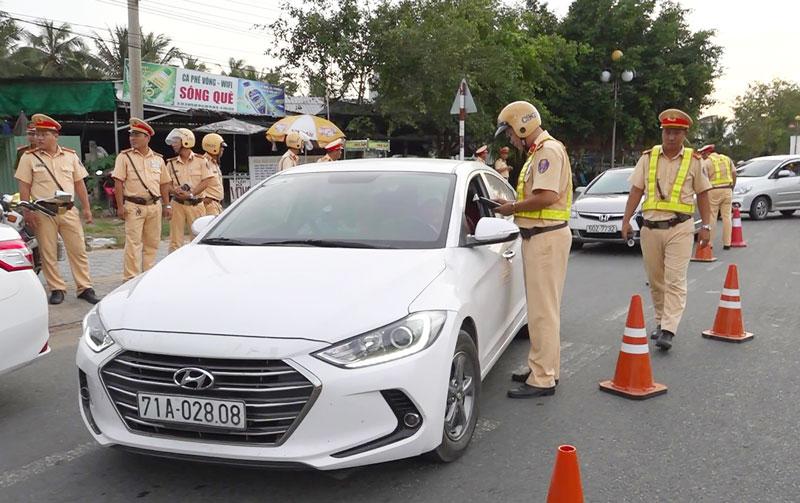 Cảnh sát giao thông kiểm tra nồng độ cồn trên tuyến quốc lộ 60. Ảnh: Q.Duy