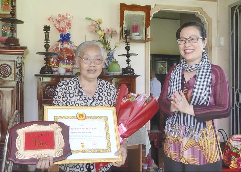 Bí thư Huyện ủy trao Huy hiệu 60 năm tuổi Đảng cho đảng viên Trương Thị Kim Hạnh. Ảnh: Kim Phụng.