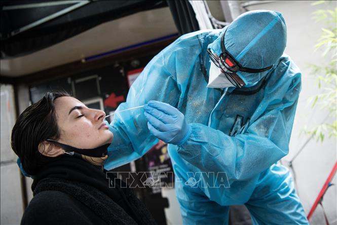 Nhân viên y tế lấy mẫu xét nghiệm COVID-19 cho người dân tại Berlin, Đức ngày 23-12-2020. Ảnh: AFP/TTXVN