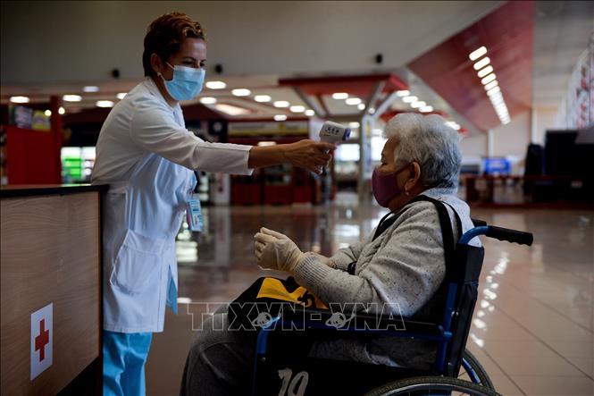 Kiểm tra thân nhiệt hành khách nhằm phòng dịch COVID-19 tại sân bay quốc tế Jose Marti ở Havana, Cuba ngày 15-11-2020. Ảnh: AFP/TTXVN