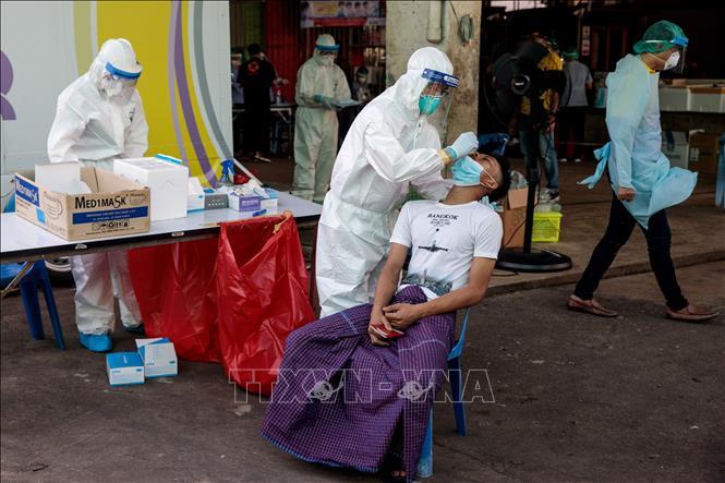 Nhân viên y tế lấy mẫu xét nghiệm COVID-19 tại Samut Sakhon, Thái Lan. Ảnh: AFP/TTXVN
