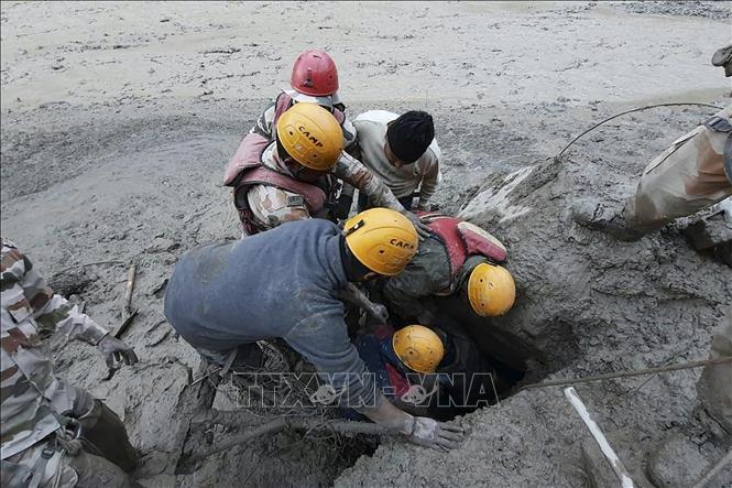 Lực lượng cứu hộ tìm kiếm nạn nhân tại khu vực bị ảnh hưởng bởi trận lũ quét ở bang Uttarakhand, Ấn Độ do vỡ sông băng trên dãy Himalaya, ngày 7-2-2021. Ảnh: AFP/TTXVN
