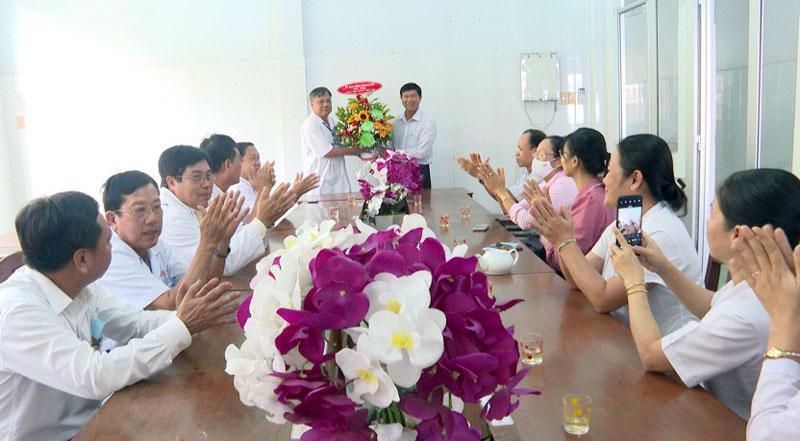 Đại diện lãnh đạo huyện tặng hoa chúc mừng tại Trung tâm Y tế huyện. Ảnh: Minh Mừng