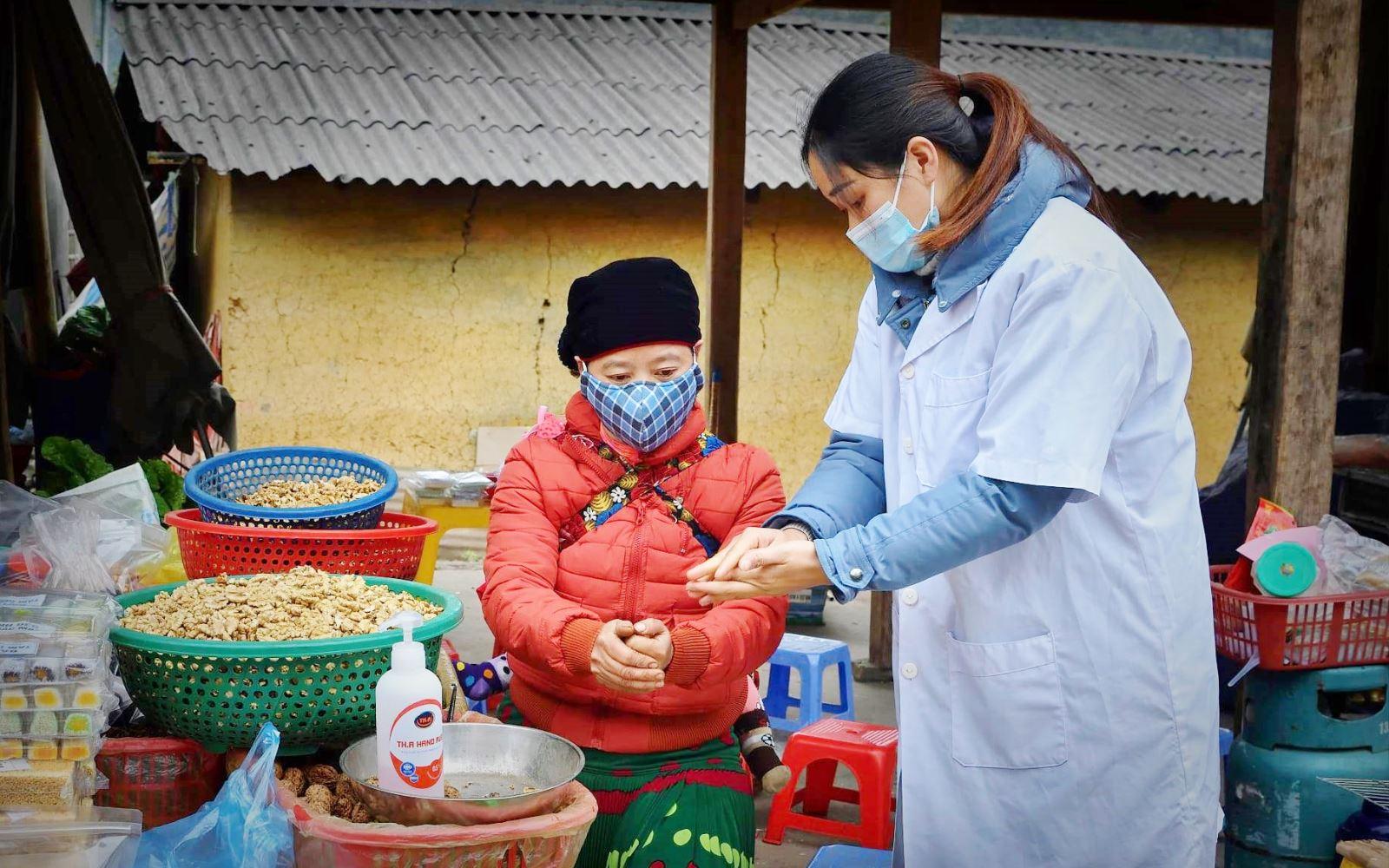 Hướng dẫn bà con tiểu thương rửa tay sát khuẩn tại chợ phiên Sà Phìn (Đồng Văn, Hà Giang). Ảnh: BYT