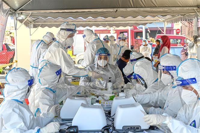 Nhân viên y tế làm việc tại điểm xét nghiệm COVID-19 ở Petaling Jaya, bang Selangor, Malaysia, ngày 21-2-2021. Ảnh: THX/ TTXVN