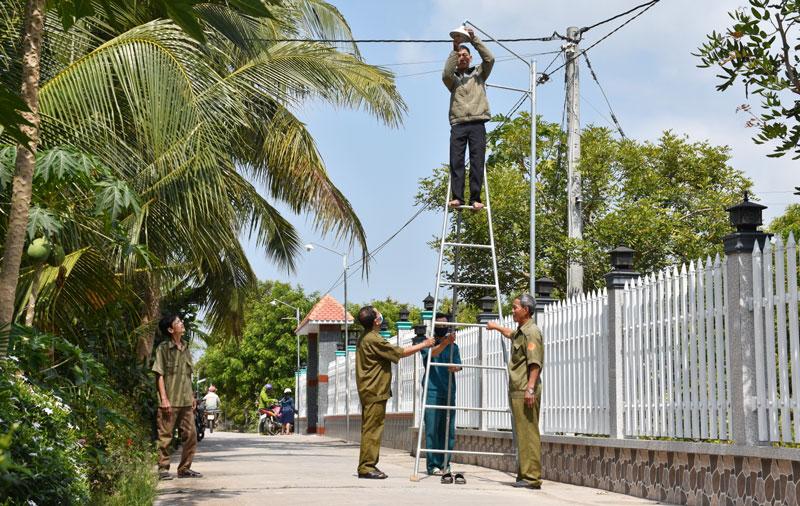 """Nhân dân ấp Phú Hiệp chung tay bảo dưỡng hệ thống đèn chiếu sáng theo mô hình """"Tuyến đường ánh sáng an ninh""""."""