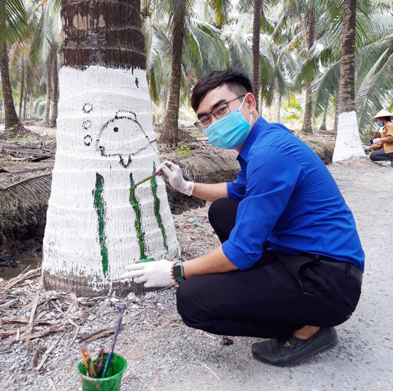 Các bạn đoàn viên vẽ hình trên những cây dừa của tuyến đường.