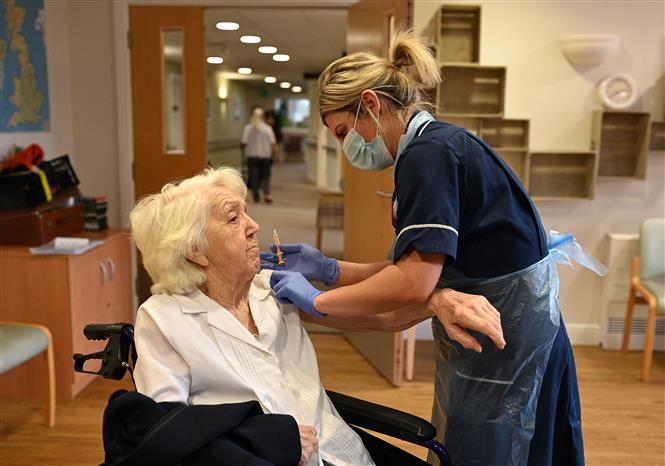 Một cụ bà được tiêm vaccine ngừa COVID-19 của AstraZeneca/Oxford tại Wigan, Anh ngày 21-1-2021. Ảnh: AFP/TTXVN