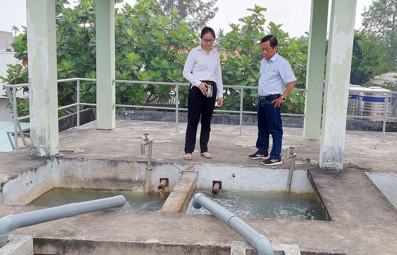 Cán bộ, nhân viên Trung tâm Nước sạch và Vệ sinh môi trường nông thôn giám sát bơm nước ngọt thô hòa mạng trước khi cấp cho người dân tại Nhà máy nước Tân Hào. Ảnh: Phan Hân