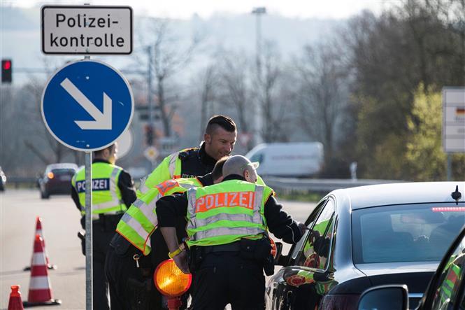 Cảnh sát Đức kiểm tra các phương tiện tại Huningue, khu vực biên giới Pháp - Đức nhằm ngăn dịch COVID-19 lây lan, ngày 16-3-2020. Ảnh: AFP/TTXVN