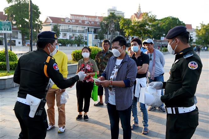 Cảnh sát phát khẩu trang miễn phí cho người dân để phòng lây nhiễm COVID-19 tại Phnom Penh, Campuchia. Ảnh: AFP/TTXVN