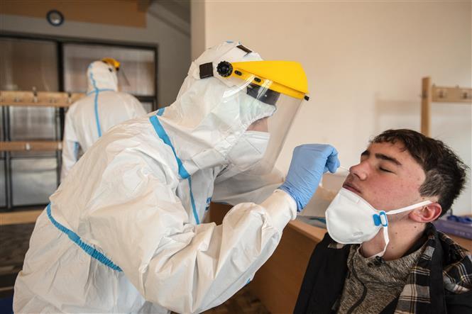 Nhân viên y tế lấy mẫu xét nghiệm COVID-19 cho bệnh nhân tại thị trấn Chodova Plana, CH Séc, ngày 3-3-2021. Ảnh: AFP/TTXVN
