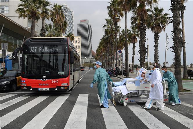 Nhân viên y tế chuyển bệnh nhân COVID-19 về lại bệnh viện sau khi được ra ngoài thư giãn tại Barcelona, Tây Ban Nha ngày 4-3-2021. Ảnh: AFP/TTXVN