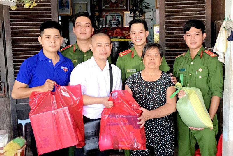 Đại úy Trọng (đứng giữa, hàng sau) trong một lần đến thăm và tặng quà cho gia đình chính sách ở xã Thới Thuận (Bình Đại) vào cuối năm 2020.