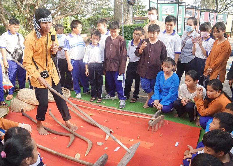 Các em học sinh được giới thiệu về các dụng cụ làm lúa.