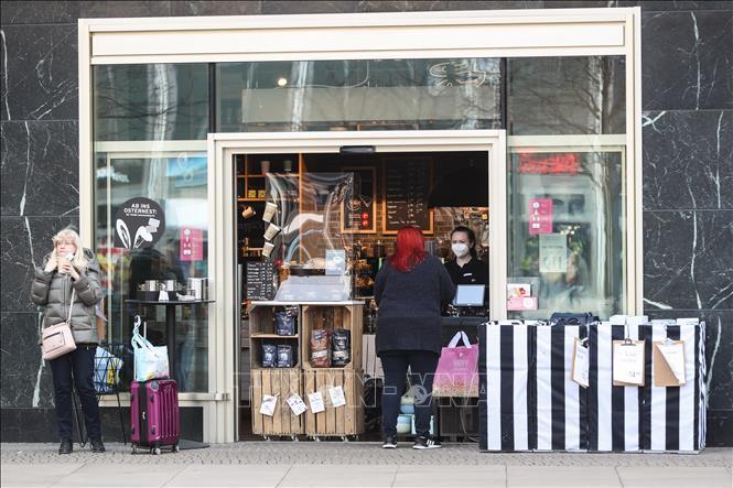 Người dân mua đồ uống tại một quán cà phê ở Berlin, Đức, trong bối cảnh lệnh hạn chế tiếp xúc được ban bố nhằm ngăn dịch COVID-19 lây lan, ngày 1-4-2021. Ảnh: THX/TTXVN
