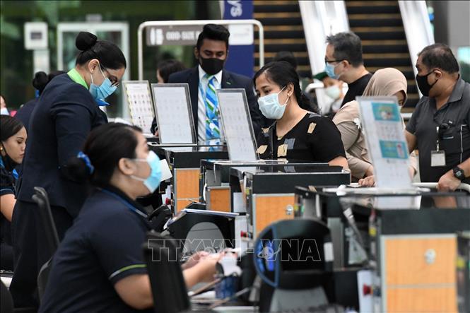 Hành khách làm thủ tục tại sân bay quốc tế Changi ở Singapore. Ảnh: AFP/TTXVN
