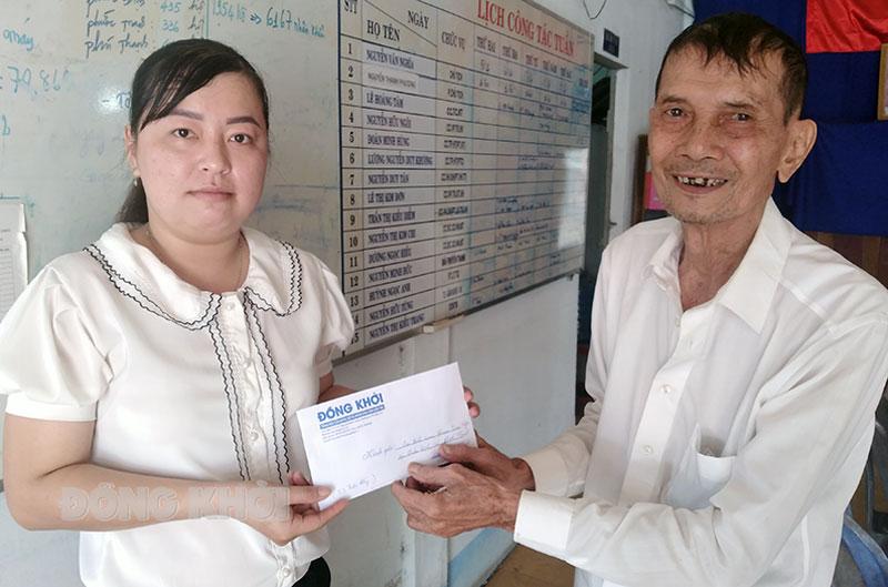 Đại diện UBND xã Phước Thạnh nhận tiền hỗ trợ cho em Phạm Kim Ngân.