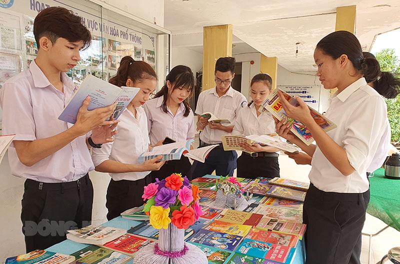 Các em học sinh Trường Năng khiếu Thể dục thể thao Bến Tre tham quan, đọc sách tại khu trưng bày sách.