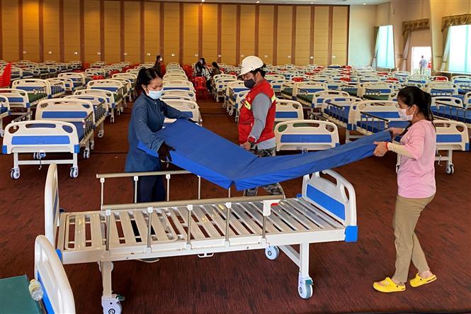 Trong ảnh: Bố trí giường bệnh bên trong một bệnh viện dã chiến điều trị cho bệnh nhân COVID-19 tại Phnom Penh, Campuchia, ngày 11-4-2021. Ảnh: AFP/TTXVN