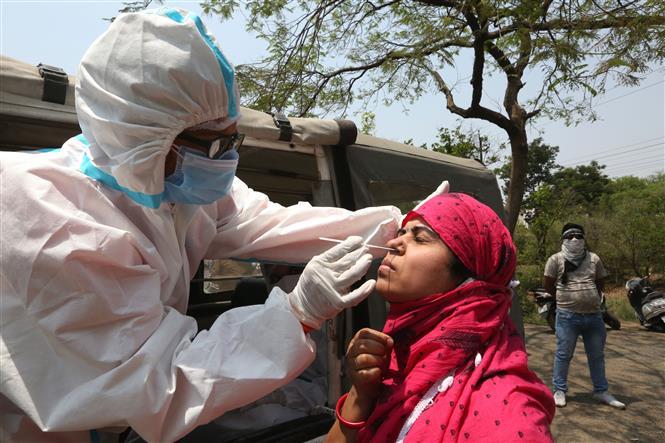 Nhân viên y tế lấy mẫu xét nghiệm COVID-19 cho người dân tại Madhya Pradesh, Ấn Độ ngày 10-4-2021. Ảnh: THX/TTXVN