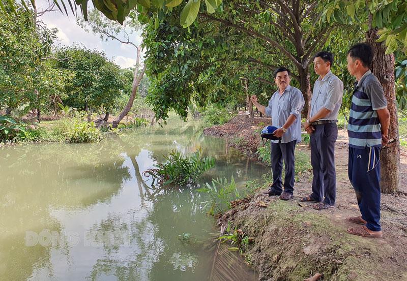 Bí thư Chi bộ ấp Thanh Yên và công chức môi trường xã Tân Thiềng kiểm tra kênh trữ nước ngọt trên địa bàn ấp.