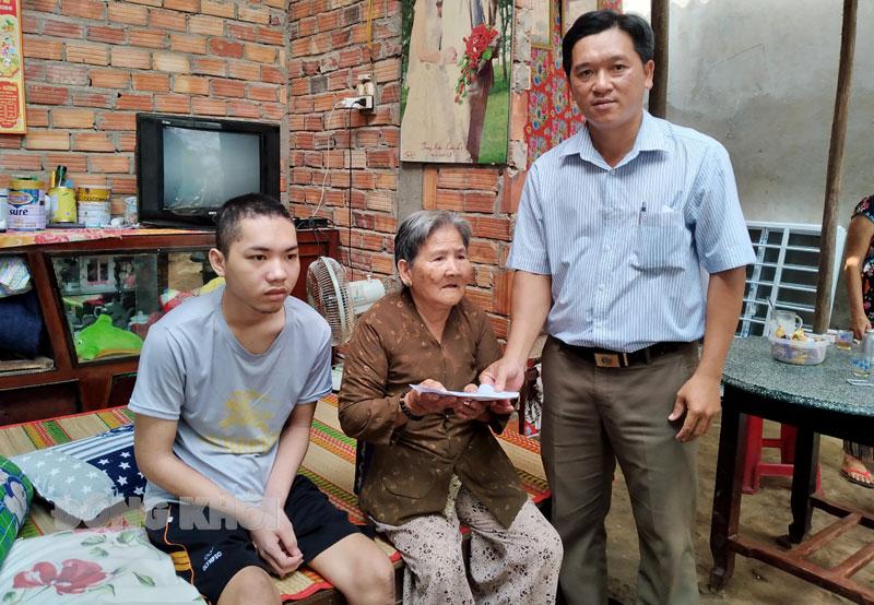 Phó chủ tịch UBND xã Thạnh Trị Lê Minh Vũ trao tiền hỗ trợ cho gia đình em Nguyễn Đăng Khoa. Ảnh: Đ. Chính