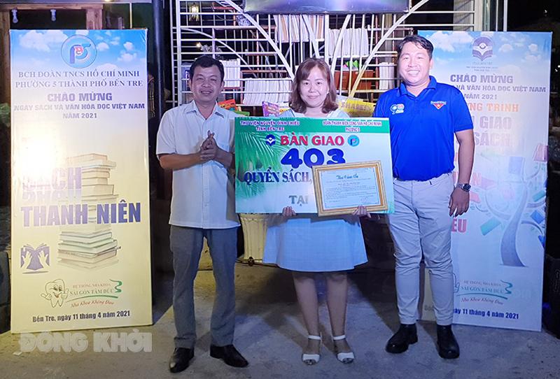 Giám đốc Thư viện Nguyễn Đình Chiểu Dương Tấn Phát (bìa trái) trao bảng tượng trưng Tủ sách thanh niên cho chủ quán cà phê Nhà Xưa.