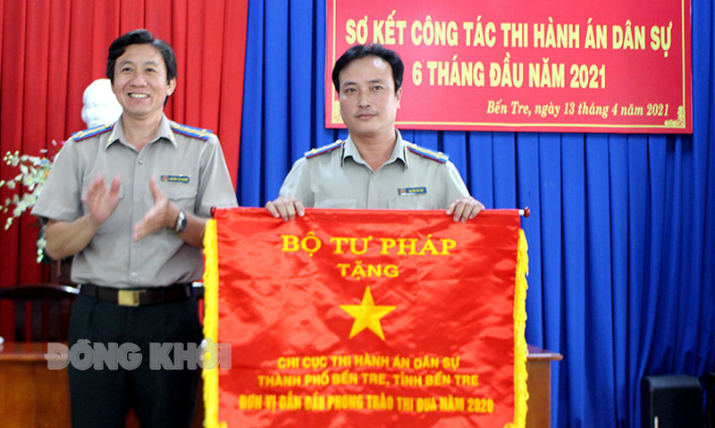 Cục trưởng Cục Thi hành án dân sự tỉnh Nguyễn Văn Nghiệp trao cờ thi đua xuất sắc của Bộ Tư pháp cho Chi cục Thi hành án dân sự TP. Bến Tre.