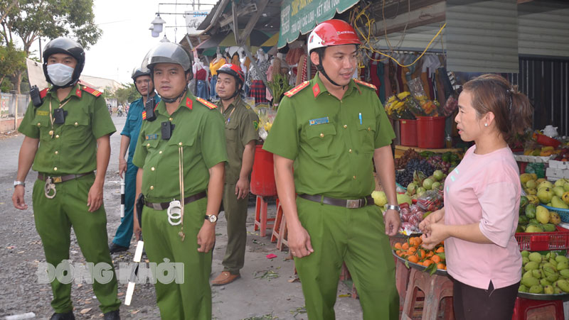 Đại úy Nguyễn Minh Cường nhắc nhở tiểu thương buôn bán đúng nơi quy định.  Ảnh: Minh Tân