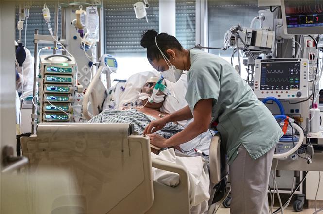 Nhân viên y tế chăm sóc bệnh nhân nhiễm COVID-19 tại một bệnh viện ở ngoại ô Paris, Pháp. Ảnh: AFP/TTXVN