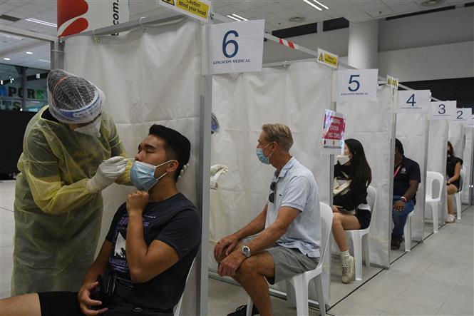 Nhân viên y tế lấy mẫu xét nghiệm COVID-19 cho người dân tại Singapore ngày 27-2-2021. Ảnh: THX/ TTXVN