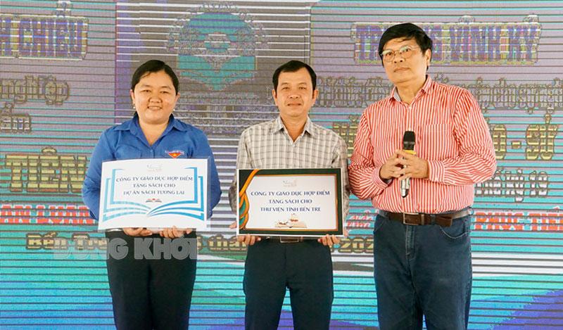 Diễn giả Trần Hữu Phúc Tiến (phải) trao bảng tượng trưng về hoạt động tặng sách cho các đơn vị.