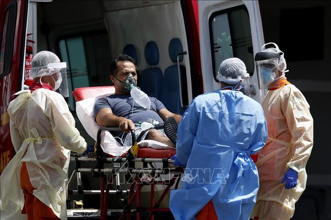 Nhân viên y tế chuyển bệnh nhân COVID-19 từ xe cứu thương vào một bệnh viện ở Brasilia, Brazil ngày 25-3-2021. Ảnh: THX/TTXVN