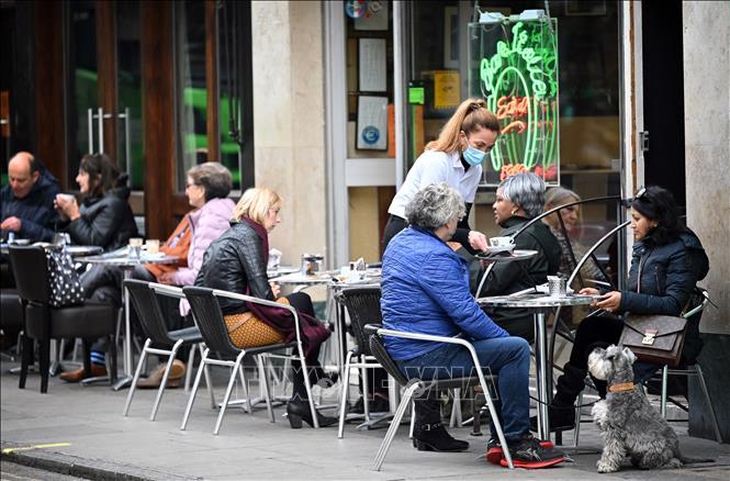 Một quán cà phê mở cửa phục vụ khách hàng tại London, Anh ngày 18-10-2020. Ảnh: AFP/TTXVN