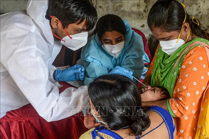 Nhân viên y tế lấy mẫu xét nghiệm COVID-19 tại Mumbai, Ấn Độ. Ảnh: AFP/TTXVN