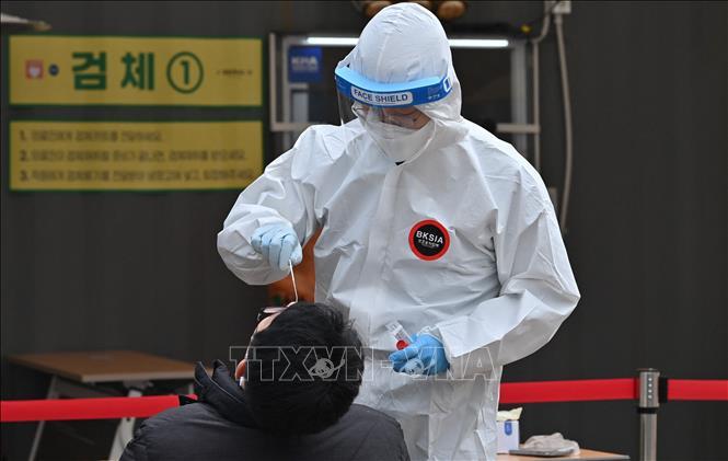 Nhân viên y tế lấy mẫu xét nghiệm COVID-19 cho người dân tại Seoul, Hàn Quốc, ngày 28-12-2020. Ảnh: AFP/TTXVN