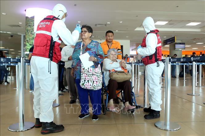 Nhân viên y tế kiểm tra thân nhiệt của hành khách tại sân bay quốc tế Mariscal Sucre ở Quito, Ecuador. Ảnh: AFP/TTXVN