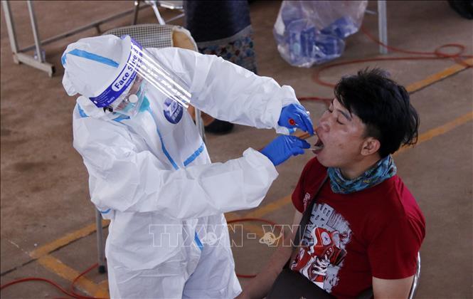 Bác sĩ lấy mẫu xét nghiệm cho một người dân Viêng Chăn tại một điểm xét nghiệm dã chiến. Ảnh: Phạm Kiên/PV TTXVN tại Lào